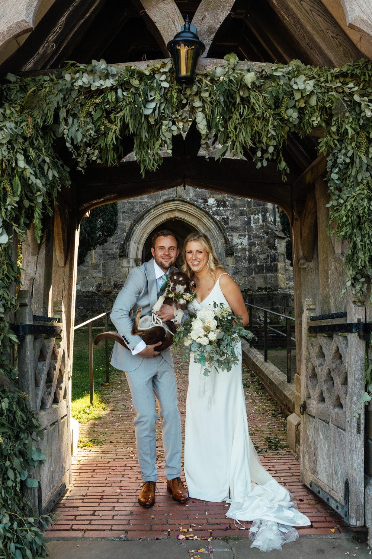 Oak Barn Wedding Matilda Delves Photography Flower Arch Church Greenery Foliage Dog Pet
