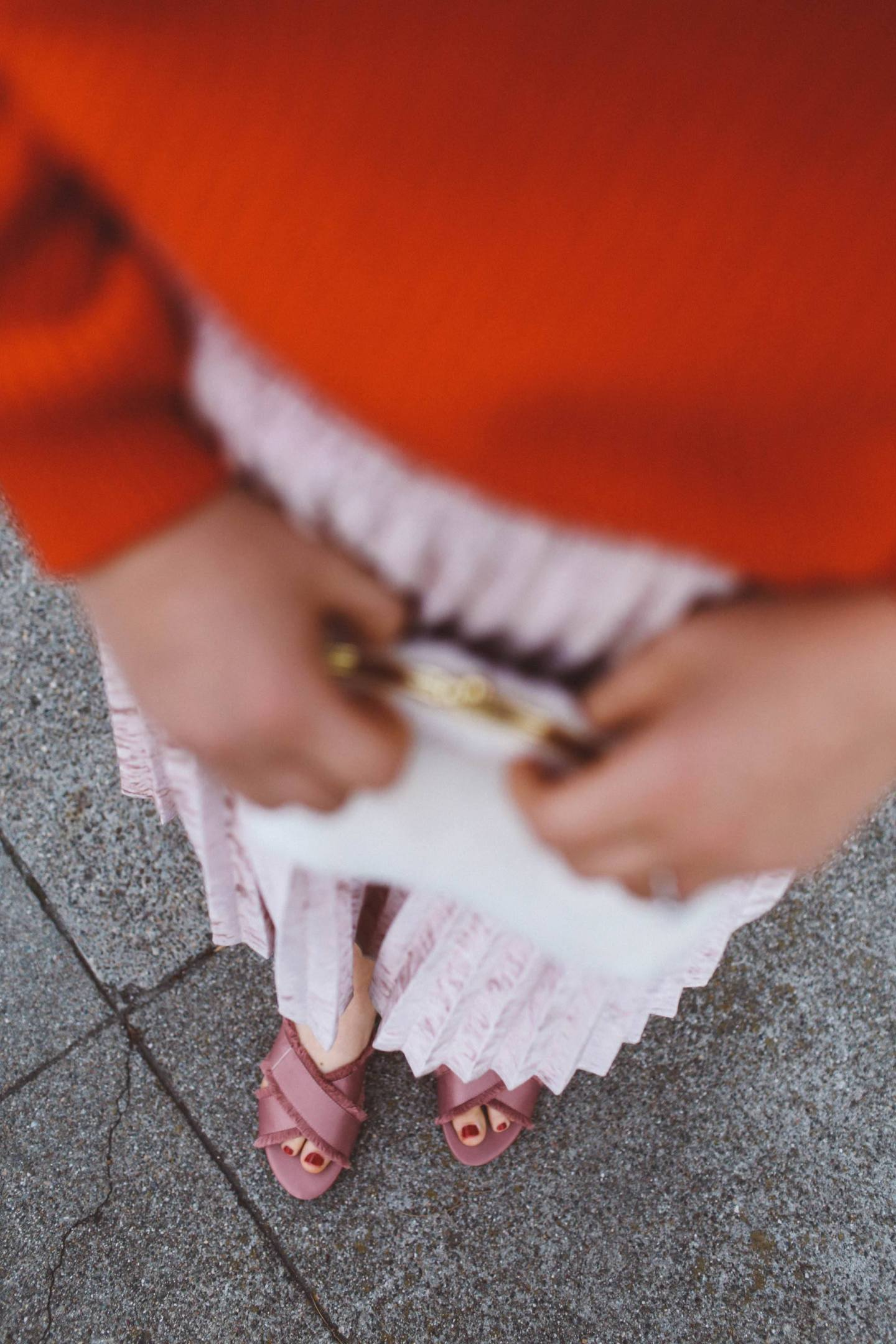 red sweater pink skirt woman white purse pink flats
