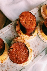 closeup of deviled eggs with chorizo links on top