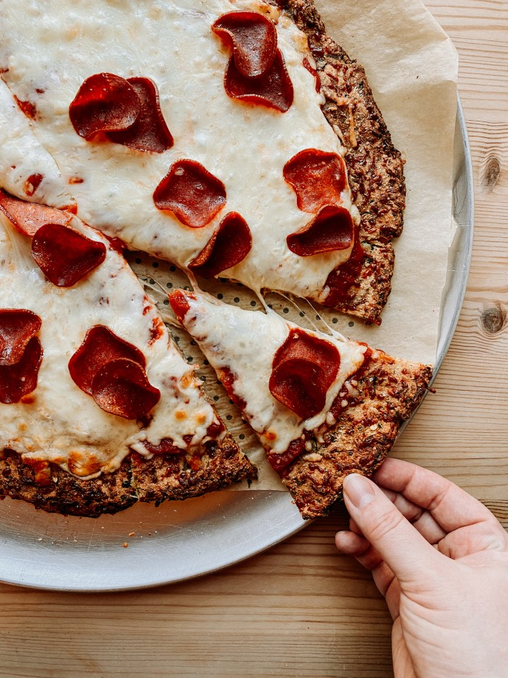 a hand grabbing a slice of pepperoni pizza using zucchini pizza crust off of a metal pan