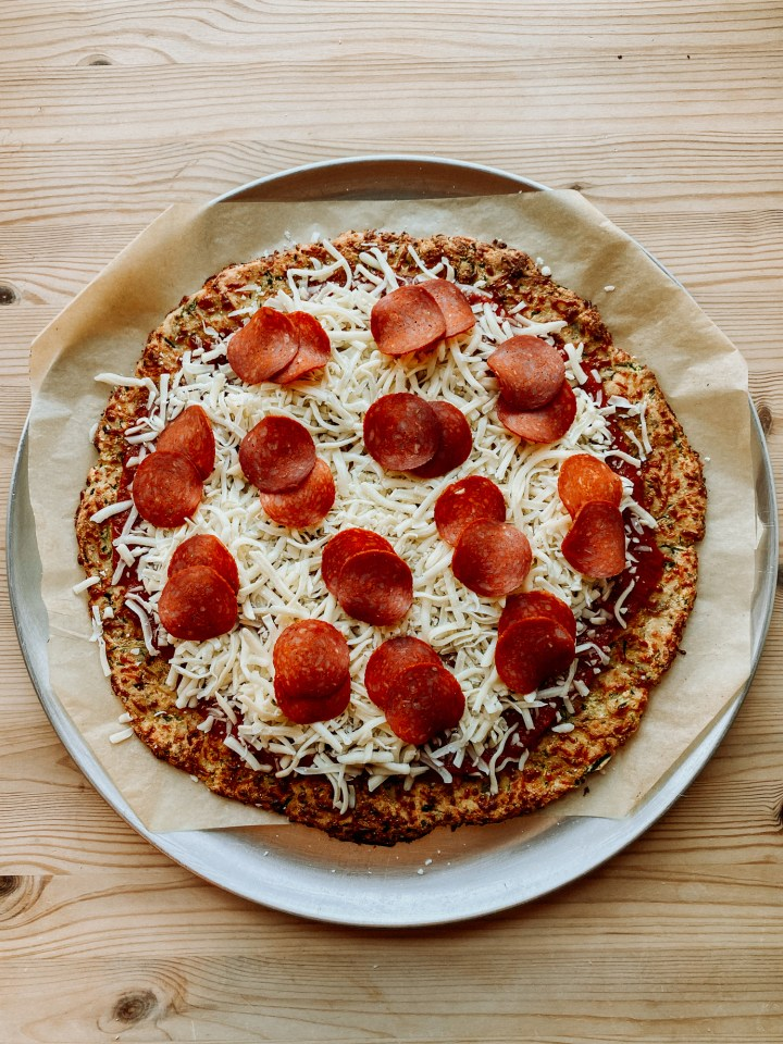 a zucchini pizza crust topped with tomato sauce, mozzarella, and pepperoni before the toppings have been baked