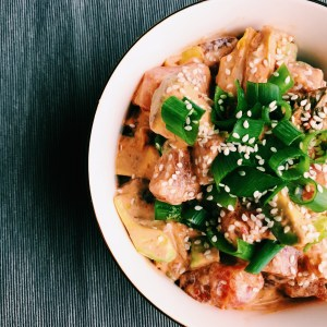 close-up of tuna fish poke with kimchi and green onions in a white bowl on a gray background