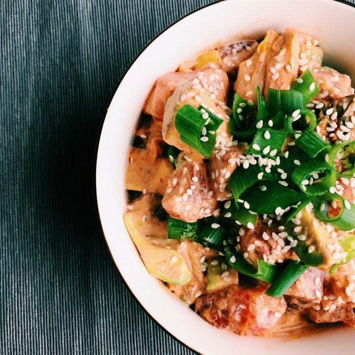 closeup of bowl of ahi kimchi poke with scallions and sesame seeds