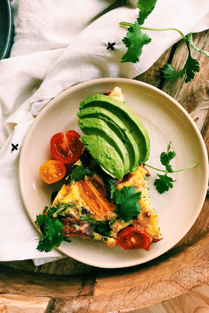 a slice of kitchen sink frittata with slices of avocado and cilantro on top