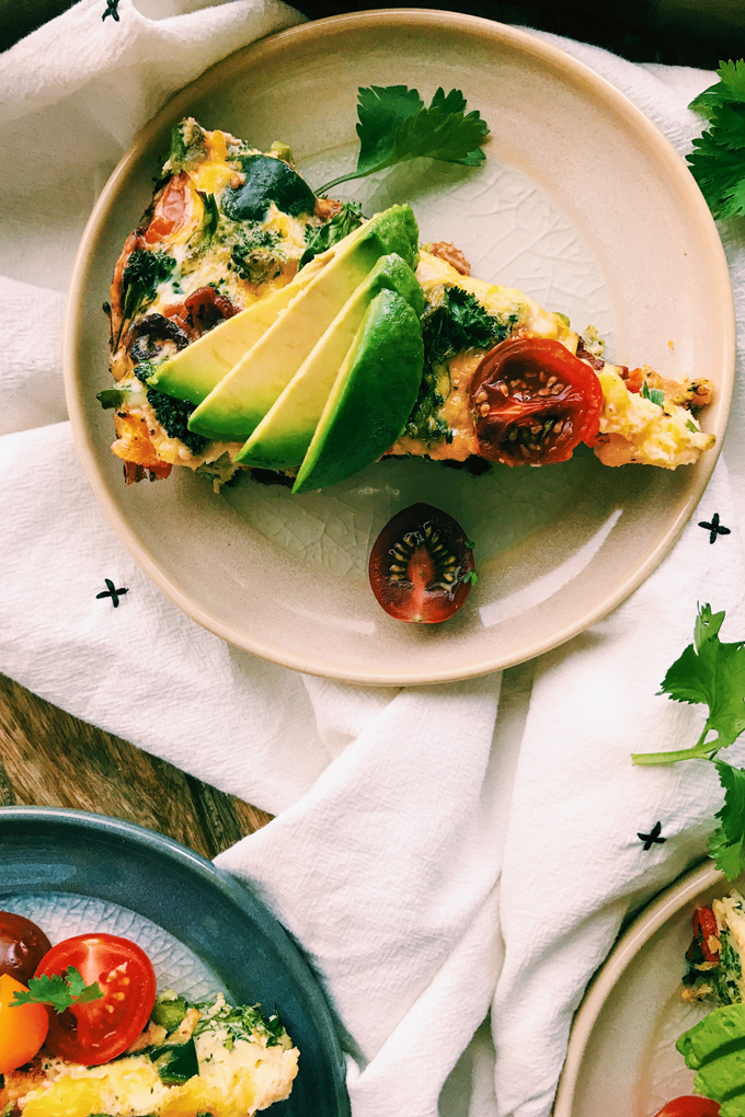 slices of frittata, sliced tomatoes, slices of avocado on tan and blue plates and white towel