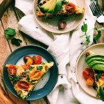 plates of breakfast frittata on a white towel laden wooden tray