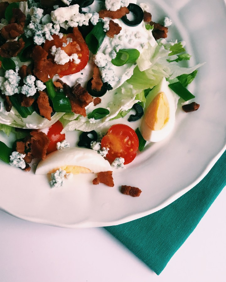 wedge salad with tomato, egg, and bacon on a white plate