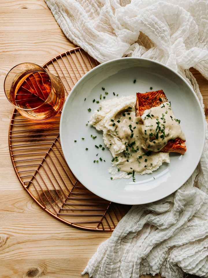 a low white bowl with salmon, mashed cauliflower, whisky cream sauce, and chives resting on a copper colored rack witha. glass of whisky resting next to the dish and a piece of light colored cloth underneath the dish
