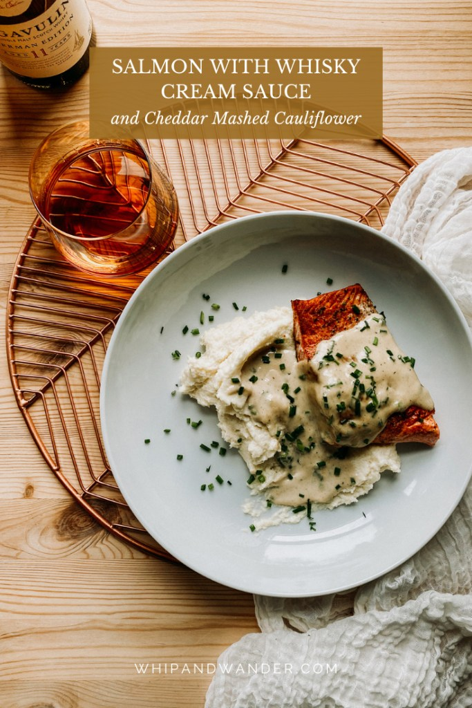 a white dish with mashed cauliflower, salmon, scotch whisky cream sauce over a copper plate rack with a glass of scotch whisky