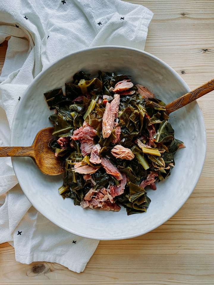 wooden serving utensils resting in a white bowl of Pressure Cooker Collard Greens with Smoked Ham Hock