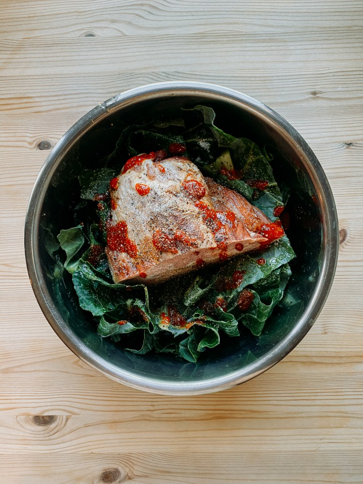 sriracha and pepper topped smoked ham hock resting on top of chopped collard greens in a metal pot