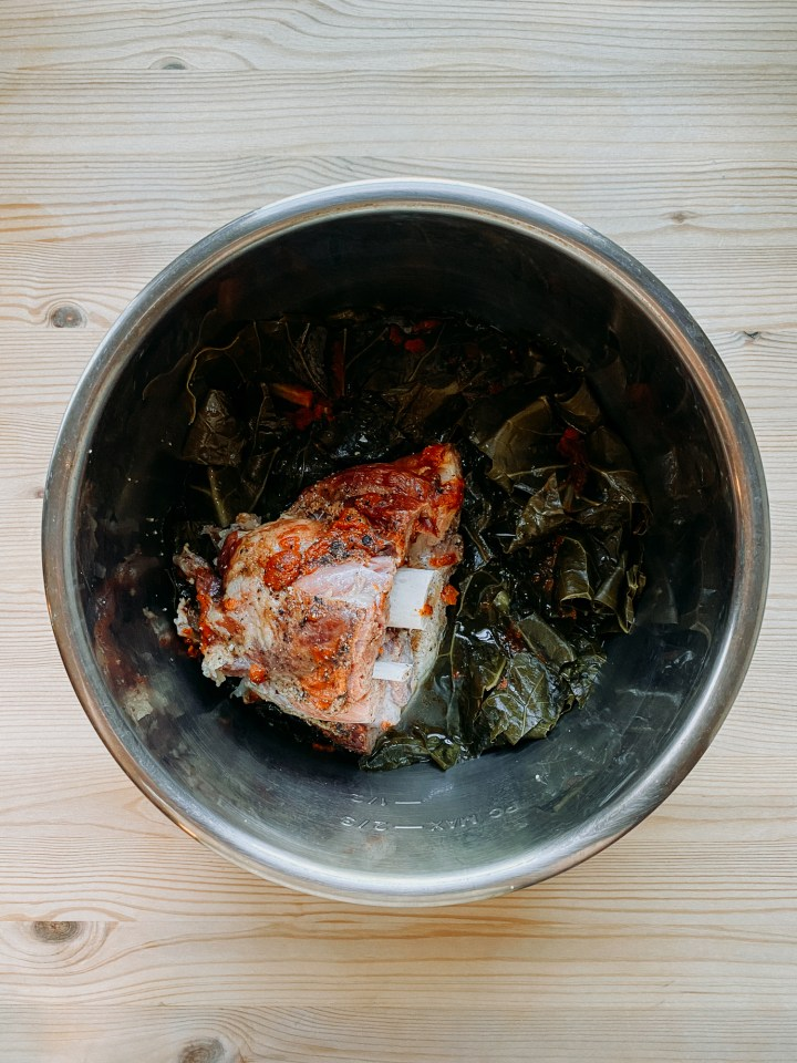 a metal pot with Pressure Cooker Collard Greens with Smoked Ham Hock inside