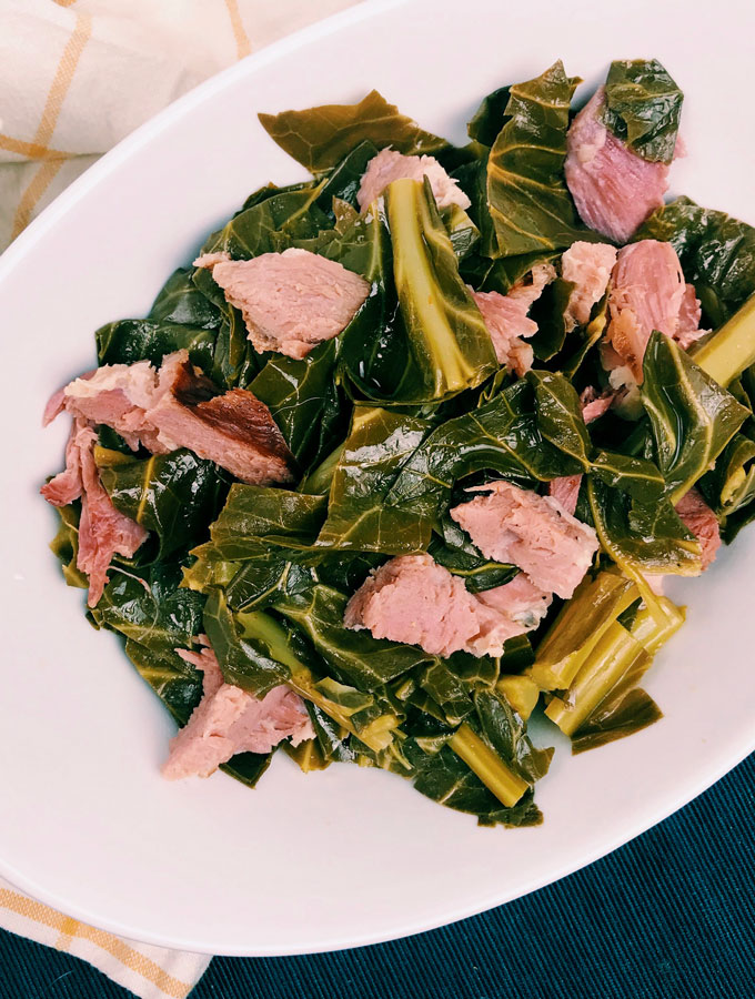 collard greensa nd ham hock in a white dish
