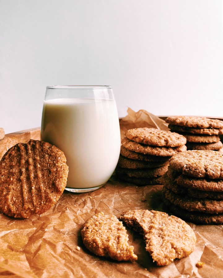 a glass of milk surrounded by Almond Peanut Butter Cookies in a brown parchment paper lined tray