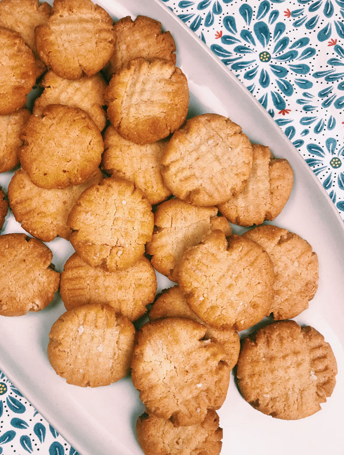Almond Peanut Butter Cookies on a white platter on a floral mat