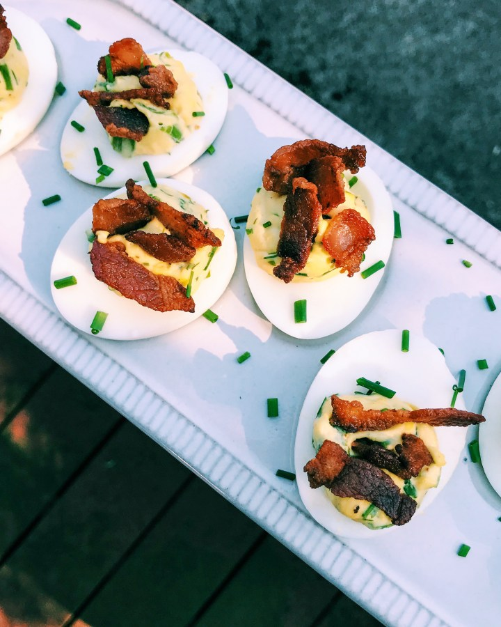 Deviled Eggs with bacon and chives on a white platter