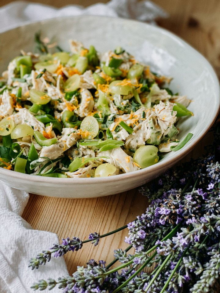 a white dish filled with French chicken salad resting on a wooden surface with a white towel and a bunch of lavender resting nearby