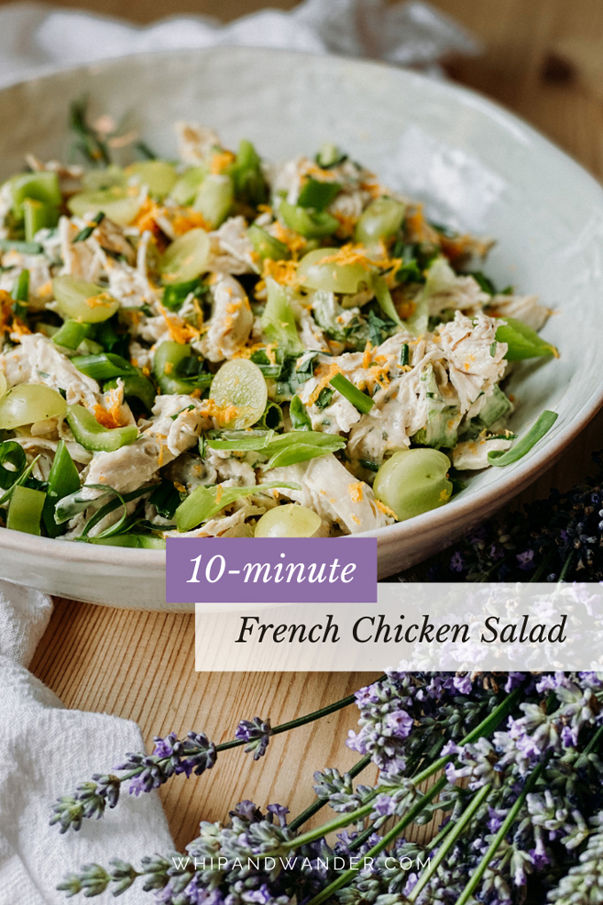 a white dish with french chicken salad, grapes, lavender, and herbs