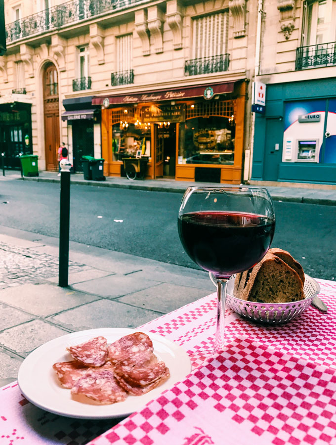 a glass of red wine and a plate of salami and bread on a white and red checkered table cloth on a patio outside