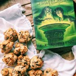 a harry potter book next to a pile of paleo rock cakes on a white towel and a wood tray