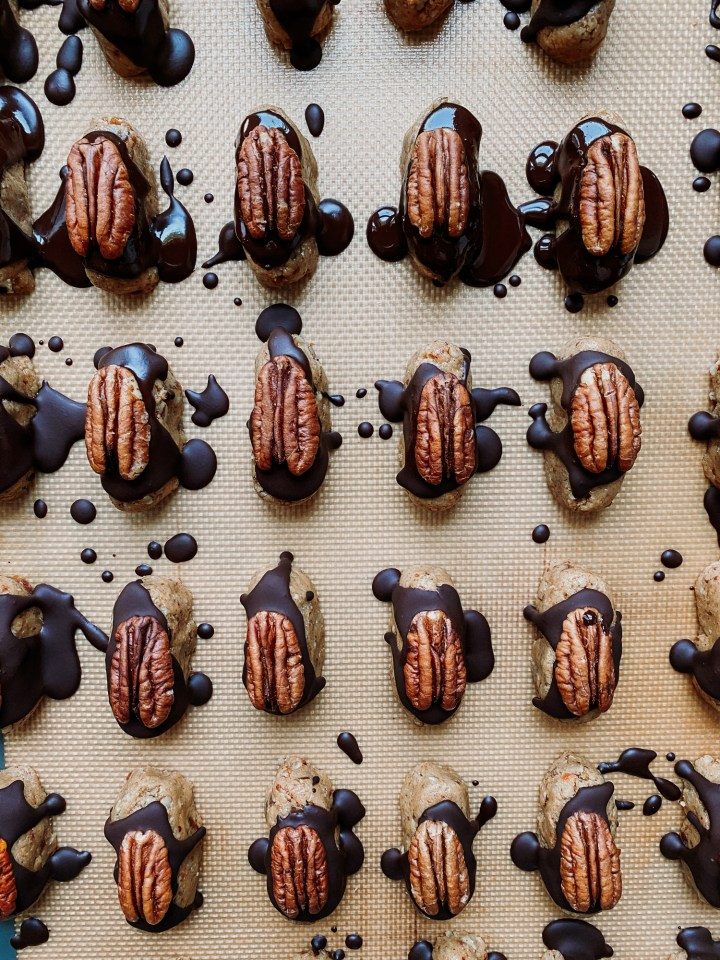 chocolate and pecan topped nut candies on a baking sheet