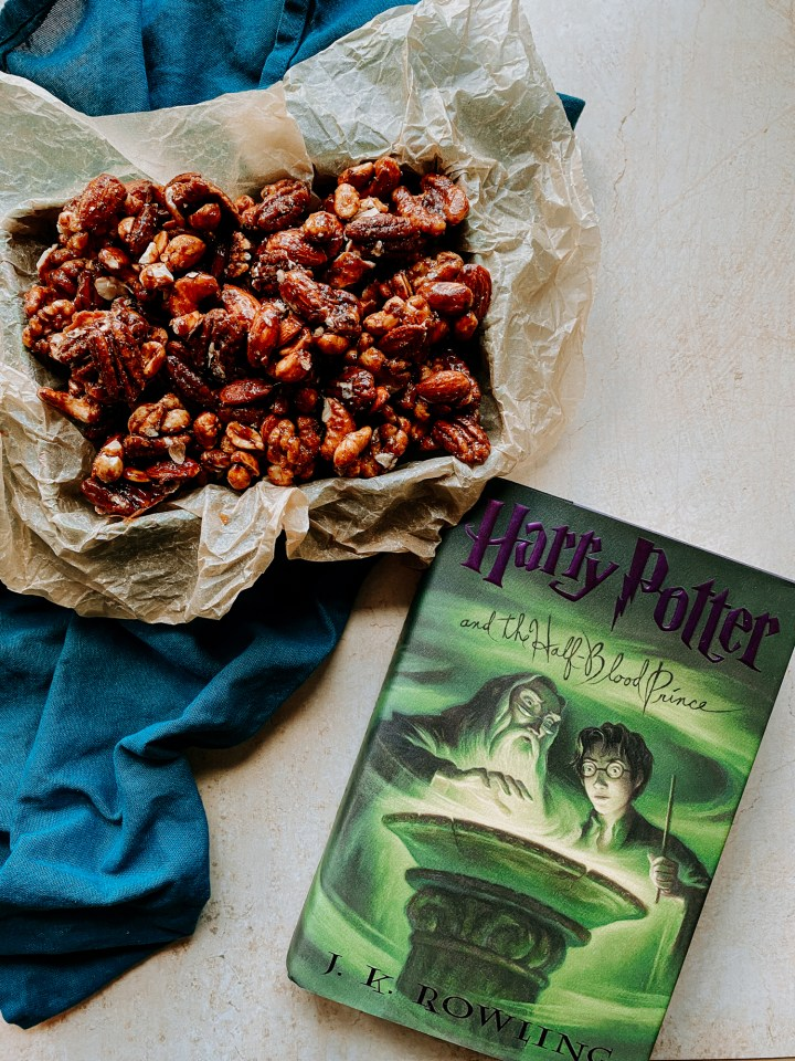 Weasleys Dragon Roasted Nuts in a parchment pined tin resting next to a harry potter book on a light colored surface with a dark blue towel