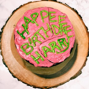 Birthday cake with red and green frosting on a tree stump
