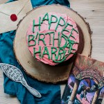 a pink and green iced chocolate birthday cake sitting on a wooden cake stand with a harry potter cook, a cake server, and a dark teal down nearby
