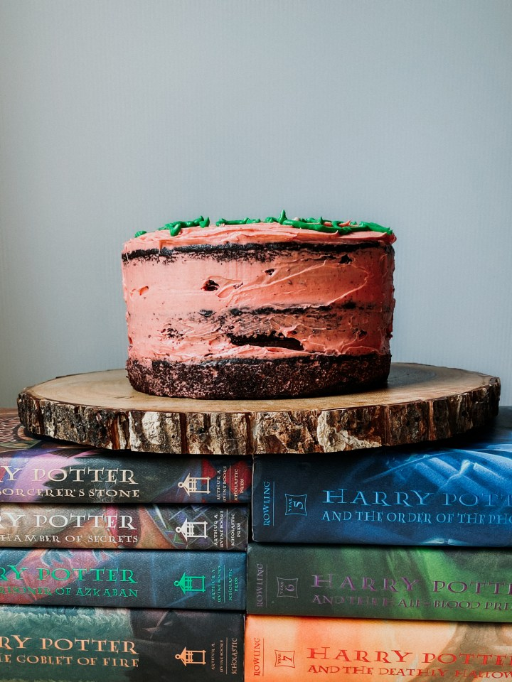 A chocolate birthday cake with pink frosting sitting on top of a stack of harry potter books