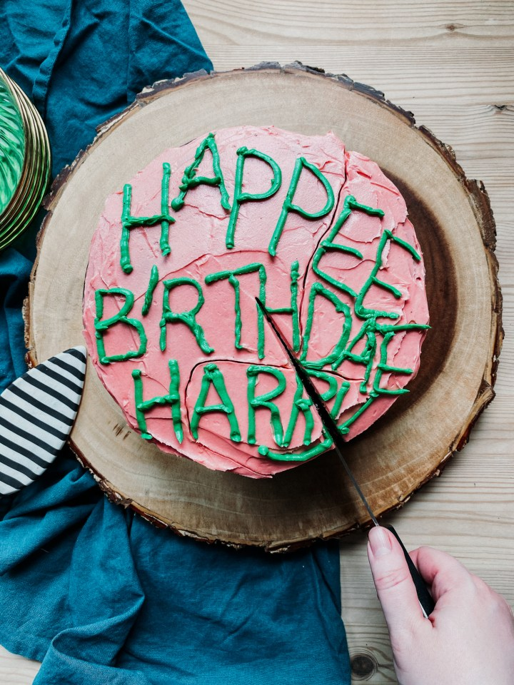 a hand cutting into a pink and green frosted birthday cake on a tree stump