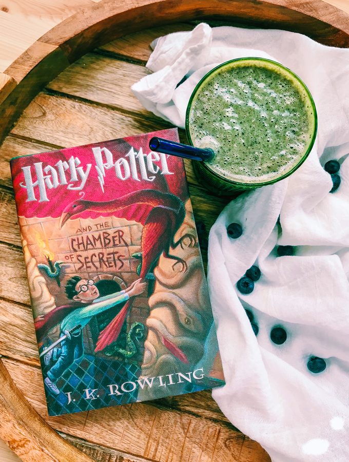 a white towel with a green smoothie and a harry potter book