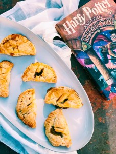 Gluten-Free Pumpkin Pasties with sausage and cheese on a white platter with a white towel and a book