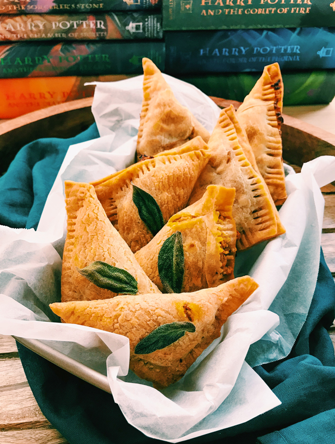 7 pumpkin pasties on a wooden tray with a teal towel