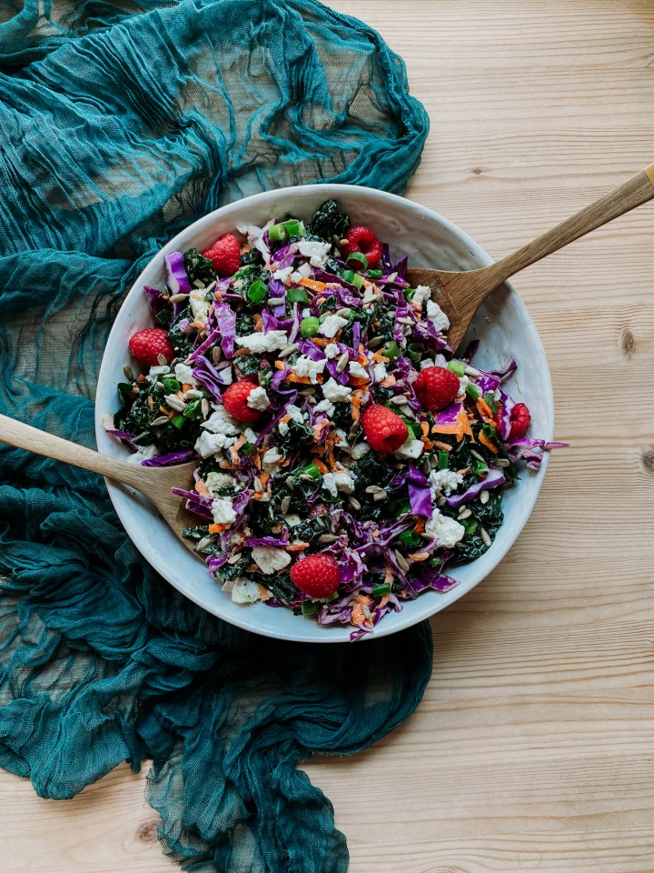 a large white serving dish filled with Creamy Kale Salad with Raspberries and Feta and two wooden salad servers resting on a dark teal cloth on a wooden surface