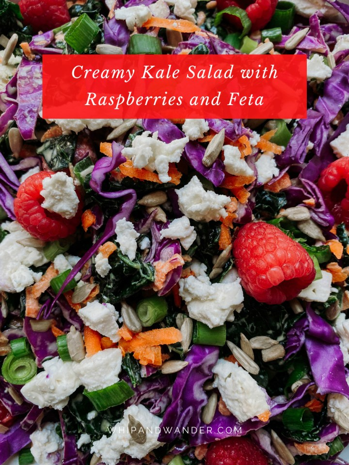 raspberries and feta top a mixture of kale, cabbage, carrots, and green onions