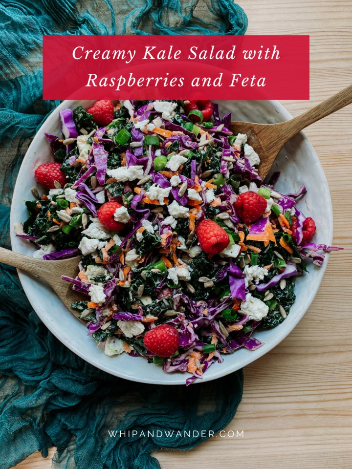 Creamy Kale Salad with Raspberries and Feta in a large white dish resting ona. wooden surface with a dark teal fabric under the bowl