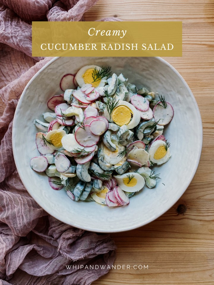 a cucumber salad in a white serving dish resting on top of a light purple cloth lined table