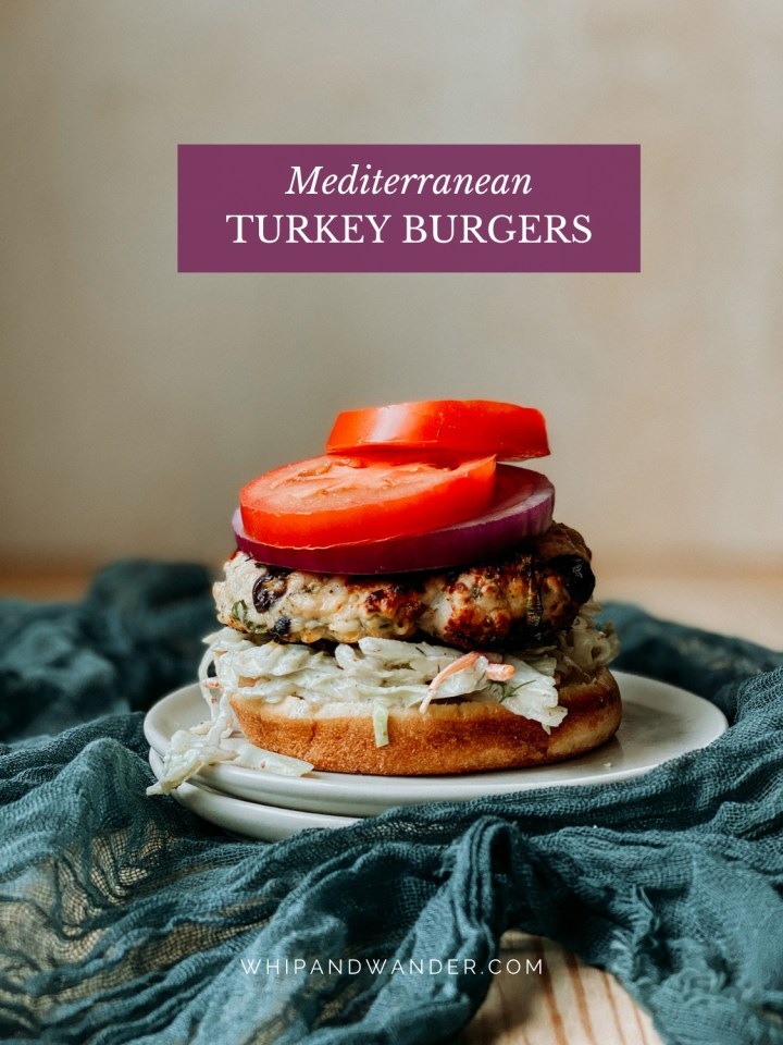 two slices of tomato and red onion on top of a Mediterranean Turkey Burger patty on a burger bun