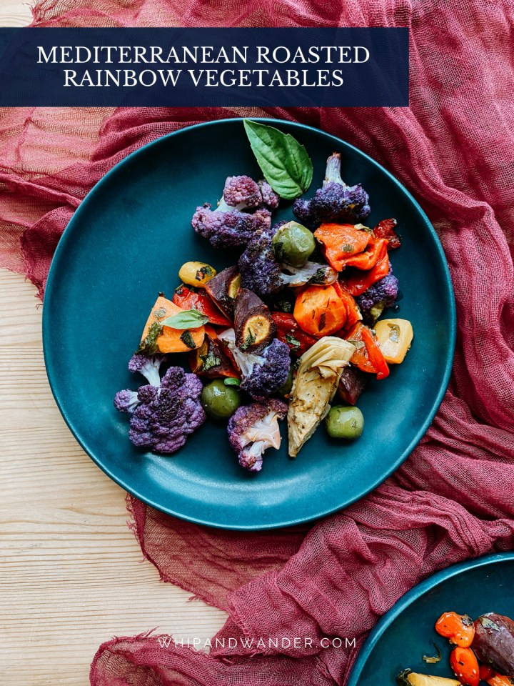 a dark teal plate on a maroon cloth with roasted vegetables on top