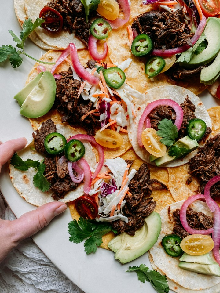 a hand grabbing a small Pressure Cooker Barbacoa Beef taco off of a platter of tacos