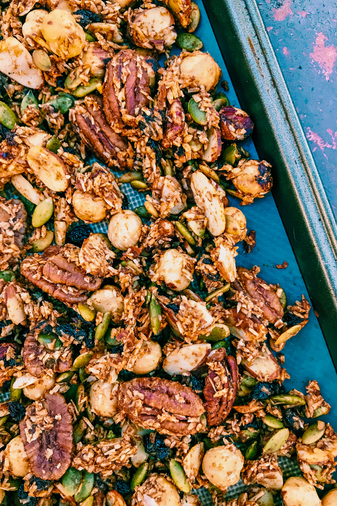 Grain-Free Pumpkin Spice Granola with nuts on a baking sheet on a blue and red background