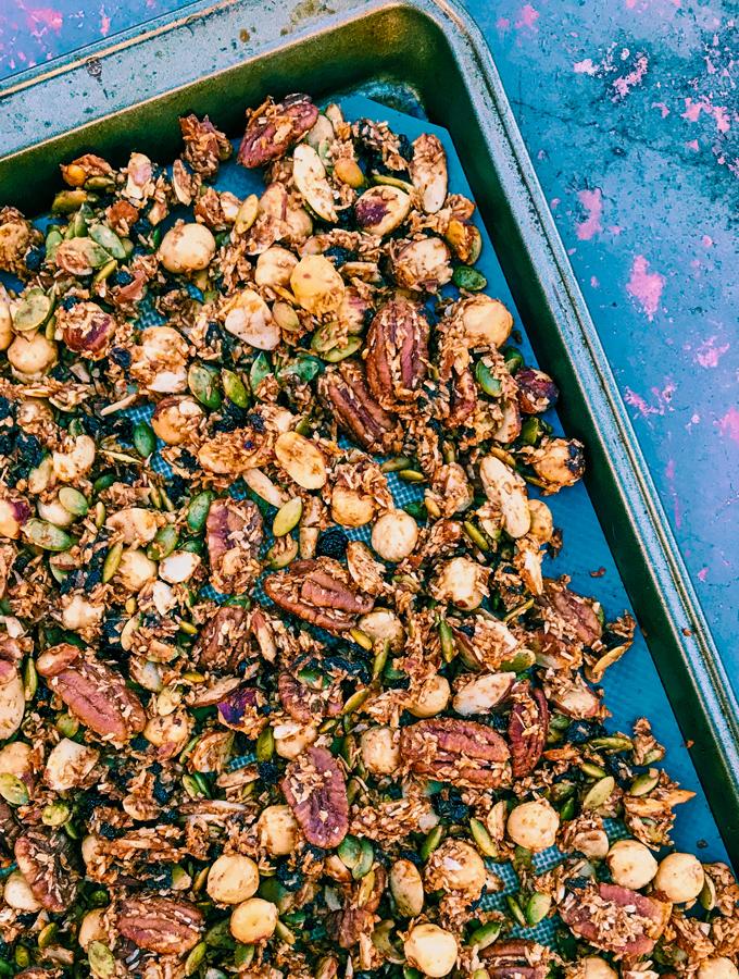 Grain-Free Pumpkin Spice Granola ona baking tray on a blue background