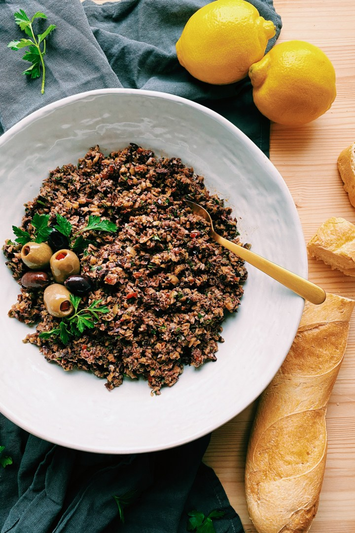 Olive Tapenade in a white bowl with a gold spoon resting in it and a baguette sliced nearby