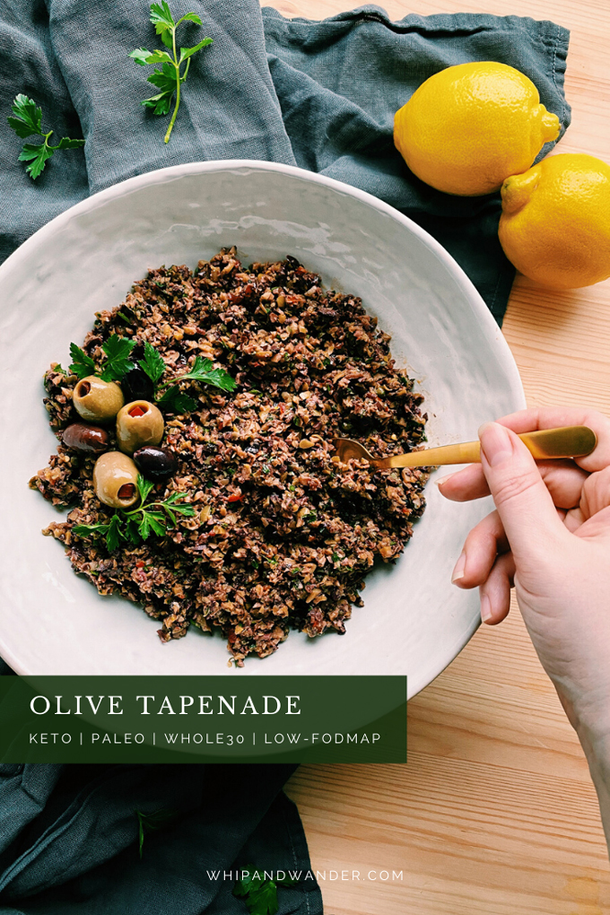 a hand holding a gold spoon in a dish of Olive Tapenade in a white bowl and two lemons resting nearby