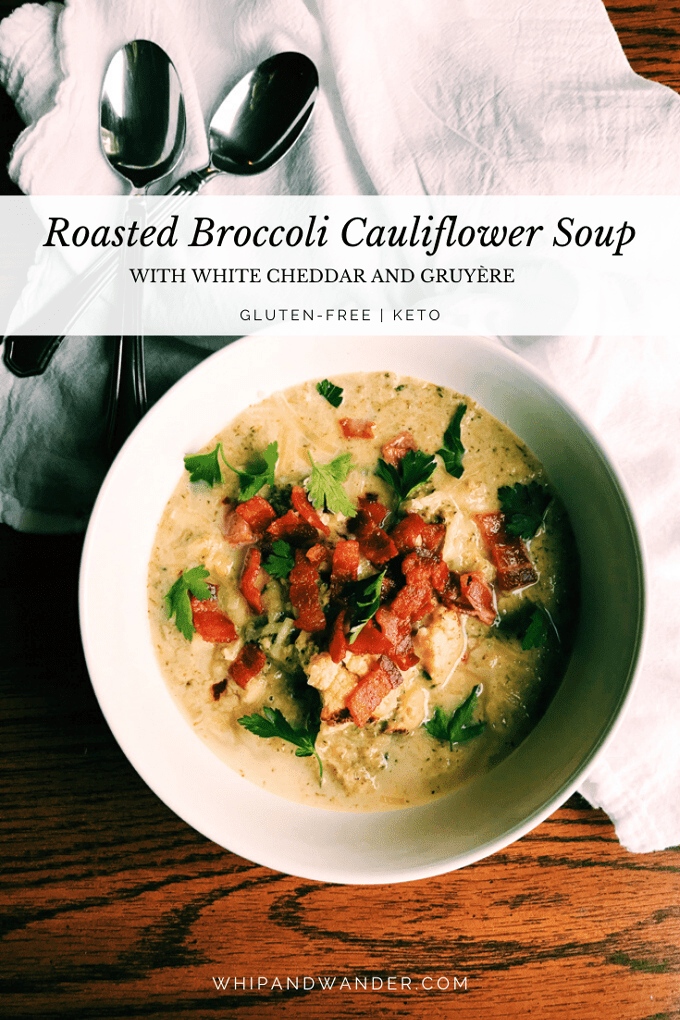 Roasted Broccoli Cauliflower Soup in a white bowl with two silver spoons on a white towel