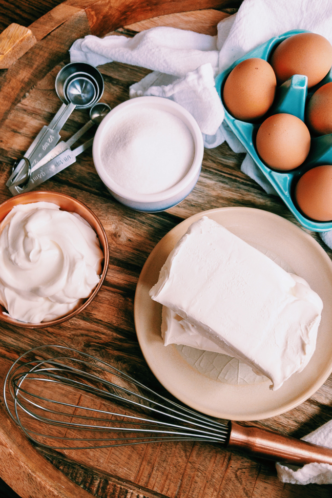 cream cheese, eggs, sour cream, monkfruit, measuring spoons on a wooden surface