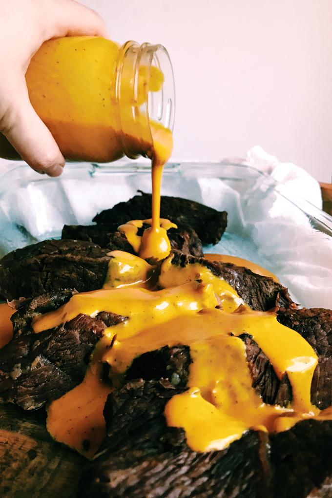 a closeup of a hand pouring Carolina gold mustard bbq sauce over boneless beef ribs from a jar