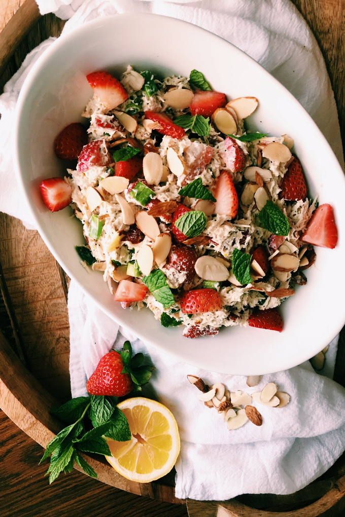 strawberry chicken salad with poppy seeds in a white bowl with a lemon