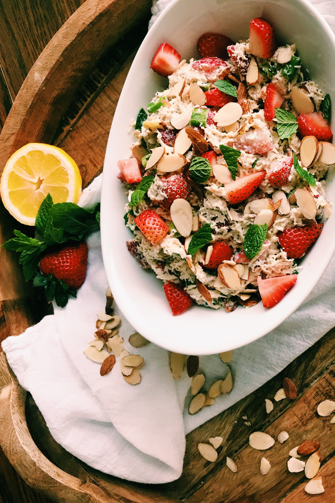 white dish with strawberry poppy seed chicken salad with mint and lemon on the side