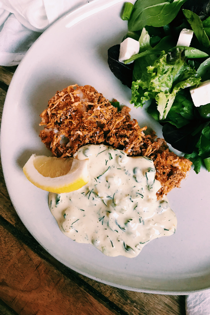 Crispy Oven Fried Fish covered in tartar sauce with a lemon on a white plate